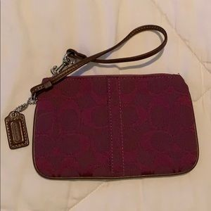 Coach wristlet in a wine color with leather strap
